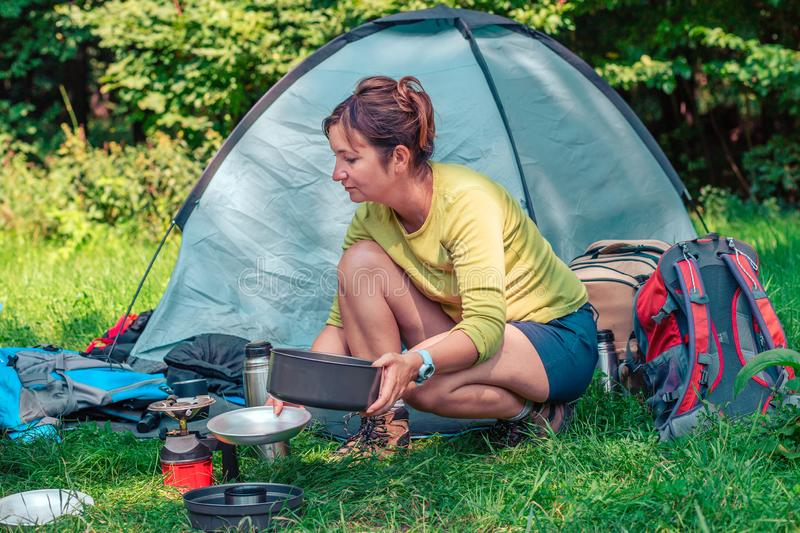 Spending a vacation on camping. Woman preparing a meal outdoor next to tent stock photos