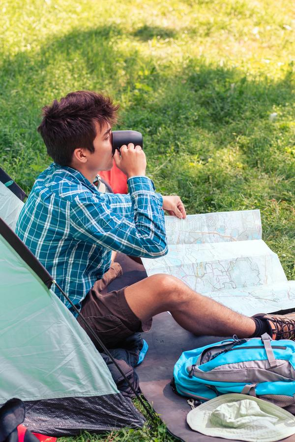 Spending a vacation on camping. Young man planning next trip and drinking a coffee stock image