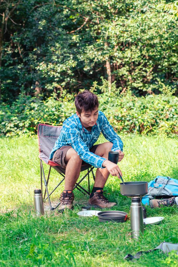 Spending a vacation on camping. Young man preparing a meal outdoor next to tent stock images