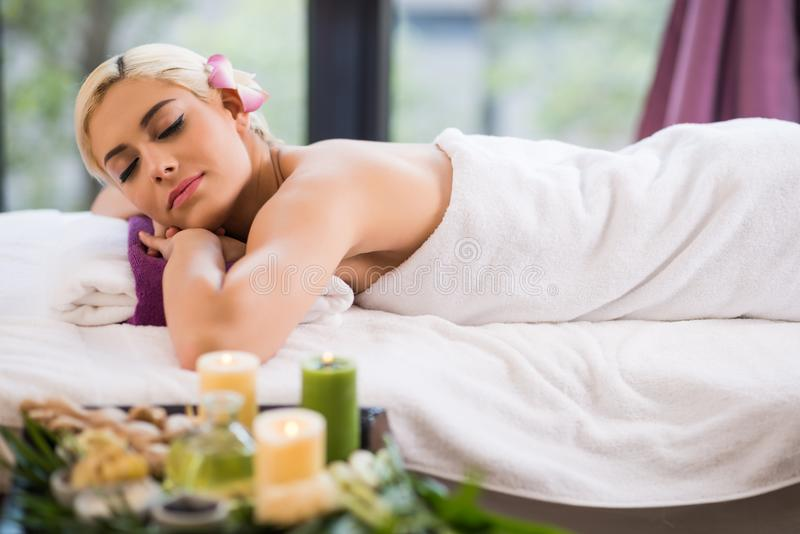 Spending Weekend in Wellness Center. Profile view of attractive young woman lying on massage table with eyes closed while spending weekend in wellness center royalty free stock photos