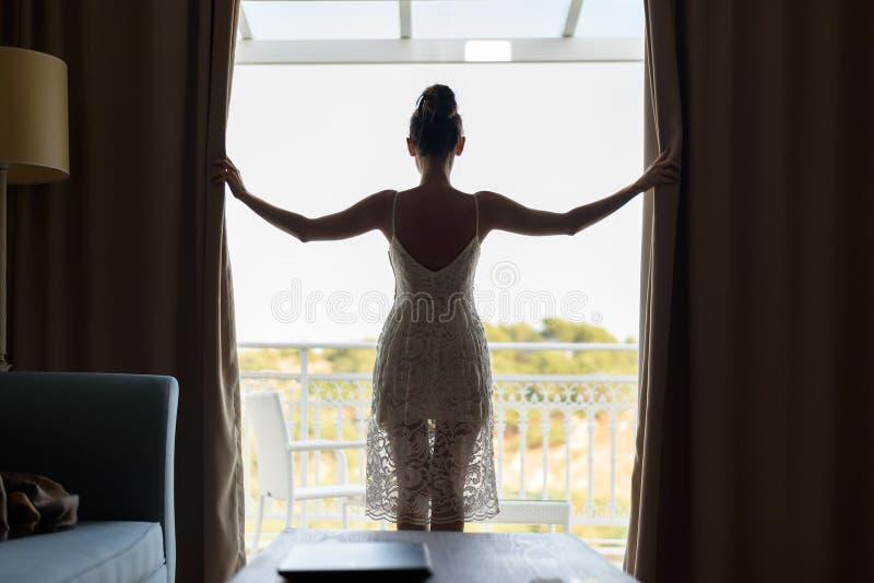 Spenslig attraktiv flicka i vita sundress från de tillbaka ställningarna på det panorama- fönstret som öppnar gardinerna royaltyfria bilder