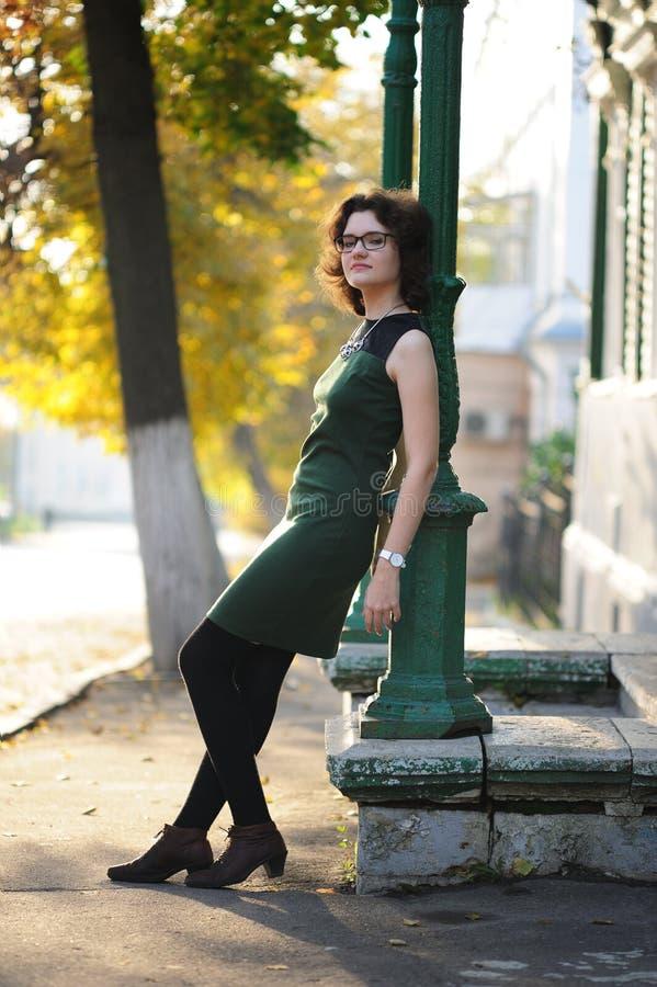 Spenslig brunettflicka i grön klänning med anblickar vid kolonn a arkivbilder
