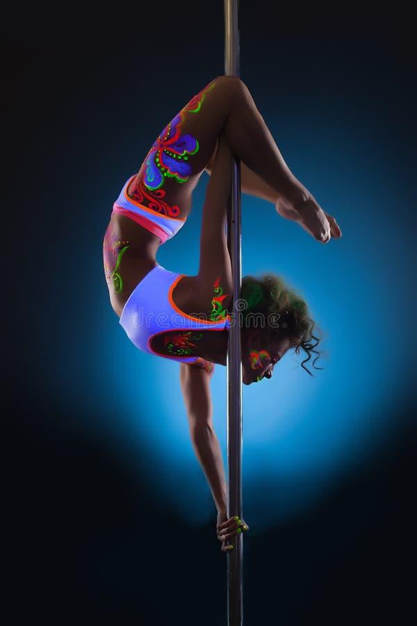 Spenslig dans för ung kvinna på pol royaltyfria bilder
