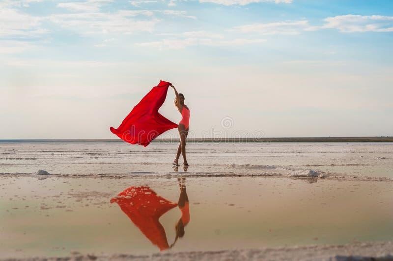Spenslig flicka på den salta sjön av Elton, Volgograd region, Ryssland Sjö Elton En flicka i en röd baddräkt och pareo, tyget D arkivbild