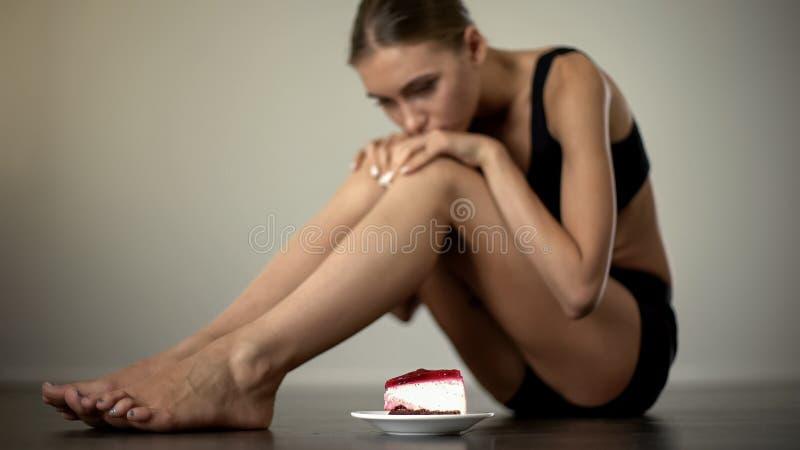 Spenslig flicka som ser kakan och att tveka att äta och att disciplinera mening och kroppen arkivbilder