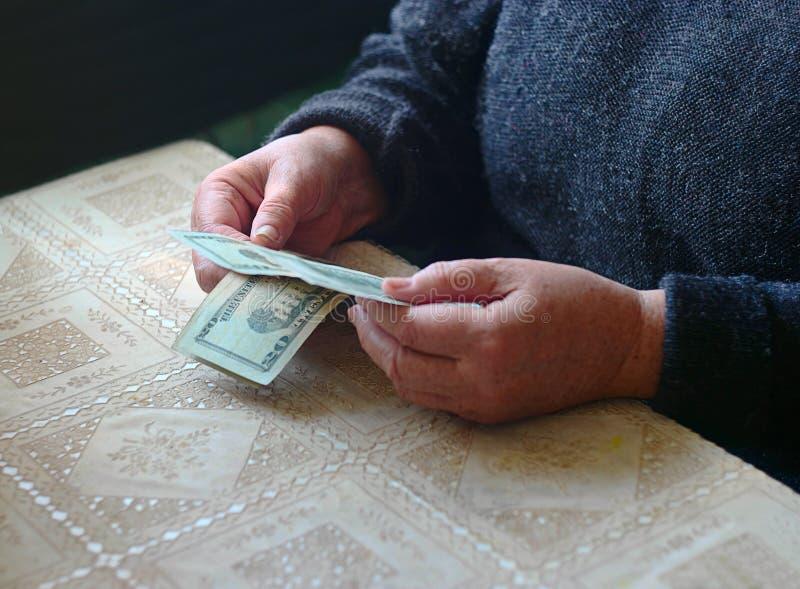 Spenslig handväska Pengar för hållande dollar för gammal kvinna kontanta i hemmastadda händer royaltyfri bild