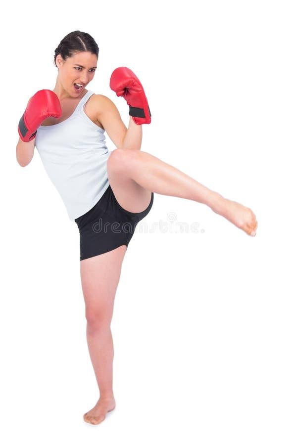 Spenslig modell med att sparka för boxninghandskar arkivbild