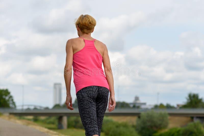 Spenslig sportig kvinna som promenerar en vandringsled arkivbilder