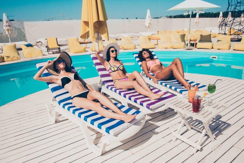 Spensliga fridsamma lugna flickor för trevlig attraktiv passform för sken som slank tunn vilar att ligga på sunbed på klubban för royaltyfri bild