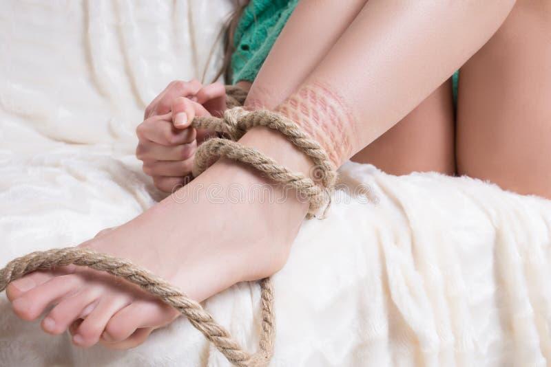 Spensliga kvinnas ben som binds med det grova repet arkivfoto