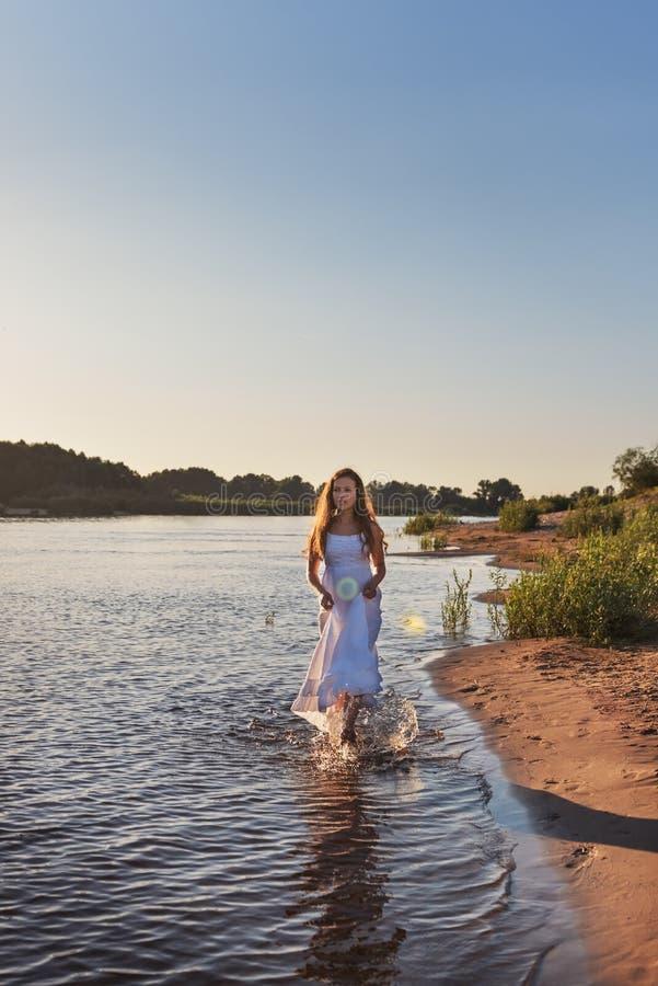 spensliga lockiga flickatonåringpromenader ner knäet i vattnet av floden i en våt vit klänning i panelljuset av soluppgången royaltyfria bilder