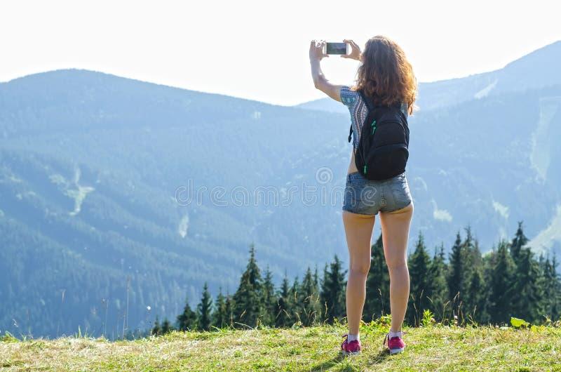 Spensligt anseende för ung kvinna på överkanten av berget och takien arkivbilder