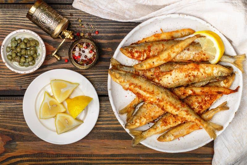 Sperlano fritto in un piatto bianco Piccoli pesci immagini stock