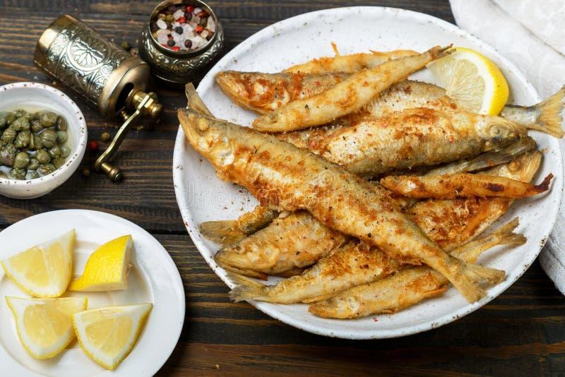 Sperlano fritto in un piatto bianco Piccoli pesci fotografia stock libera da diritti