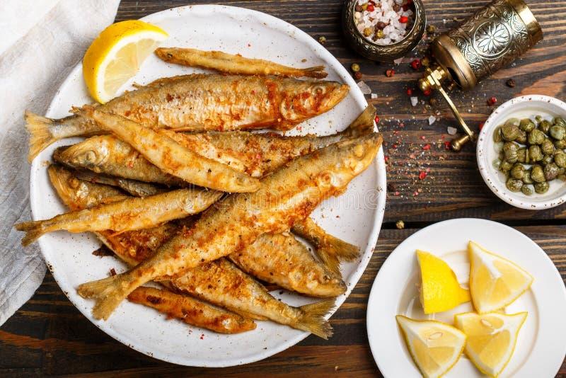 Sperlano fritto in un piatto bianco Piccoli pesci fotografia stock