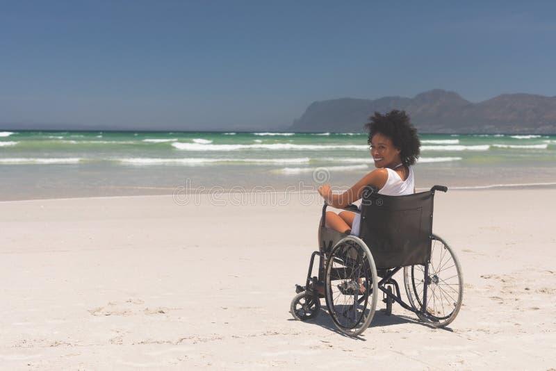 Sperrung der jungen Frau, die auf Rollstuhl am Strand sitzt stockfoto