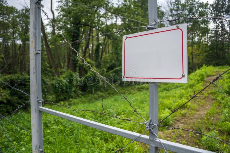 Sperrzone eingezäunt mit einem Stacheldrahtzaun Tor mit dem Vorhängeschloß geschlossen zum Schlüssel Grenze von Zuständen stockfotografie