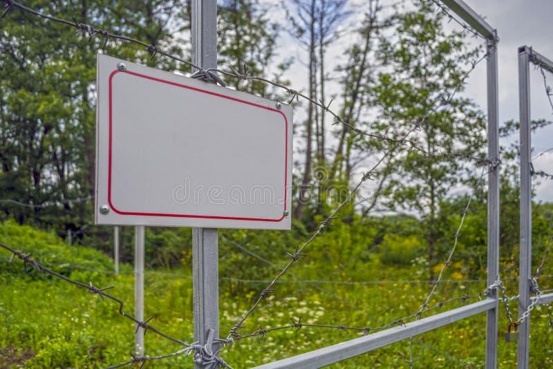 Sperrzone eingezäunt mit einem Stacheldrahtzaun Tor mit dem Vorhängeschloß geschlossen zum Schlüssel Grenze von Zuständen stockfoto
