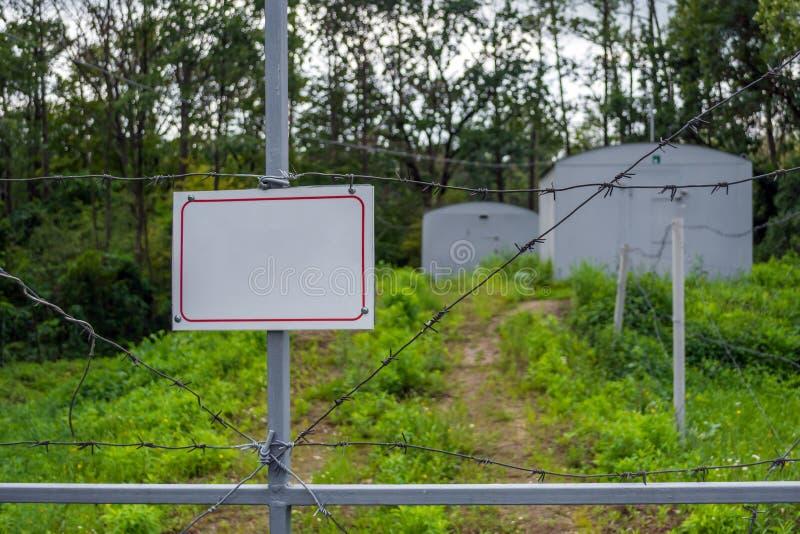 Sperrzone eingezäunt mit einem Stacheldrahtzaun Tor mit dem Vorhängeschloß geschlossen zum Schlüssel Grenze von Zuständen lizenzfreie stockfotografie