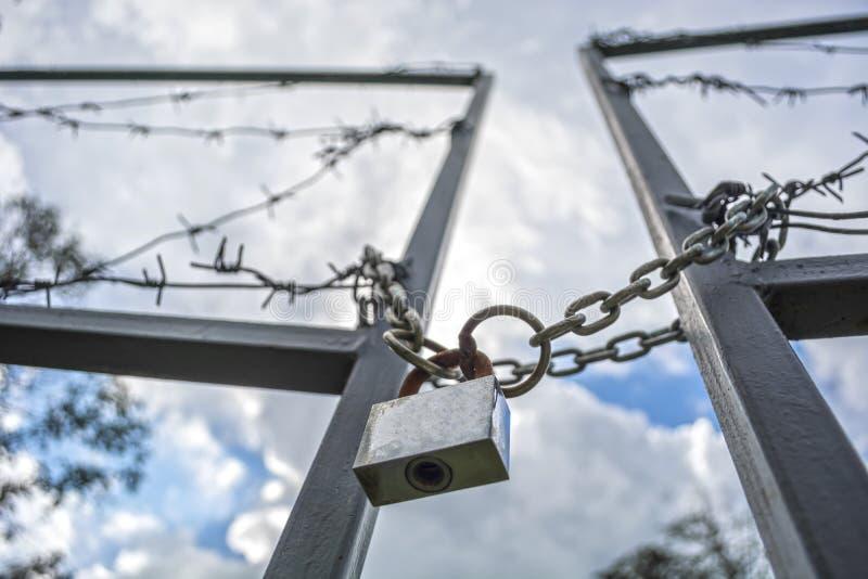 Sperrzone eingezäunt mit einem Stacheldrahtzaun Tor mit dem Vorhängeschloß geschlossen zum Schlüssel Grenze von Zuständen stockfotos