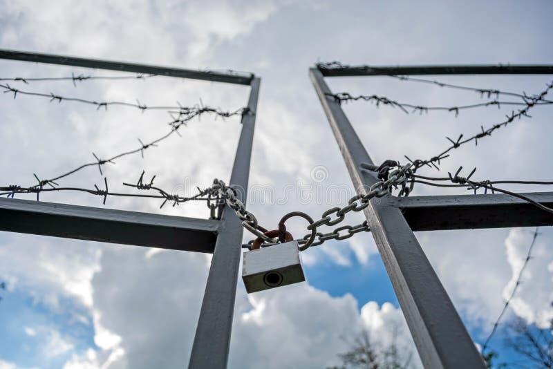 Sperrzone eingezäunt mit einem Stacheldrahtzaun Tor mit dem Vorhängeschloß geschlossen zum Schlüssel Grenze von Zuständen stockbild