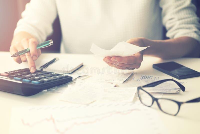 Spese di famiglia - fatture calcolarici della donna a casa immagine stock
