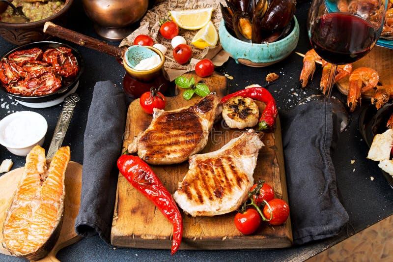 Spese generali della tavola di cena Arrostito delizioso assortito mi arrostisce col barbecue immagini stock libere da diritti