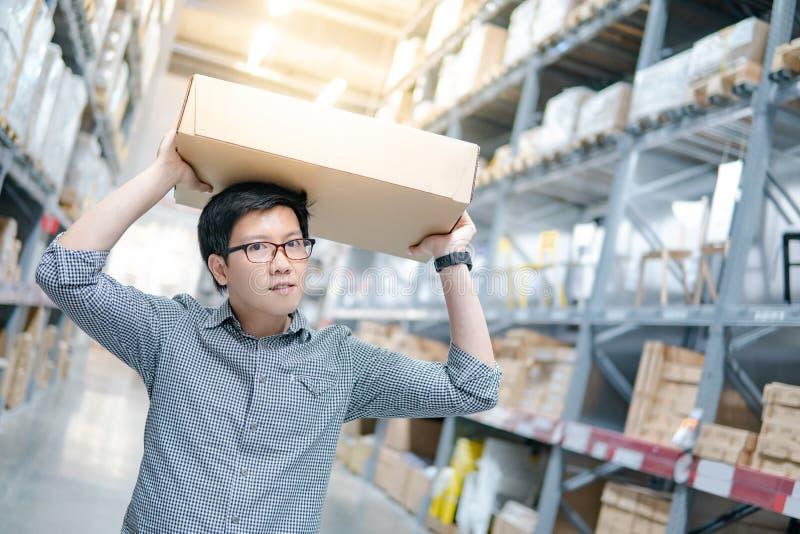 Spese generali di trasporto della scatola di cartone dell'uomo asiatico in magazzino immagini stock libere da diritti