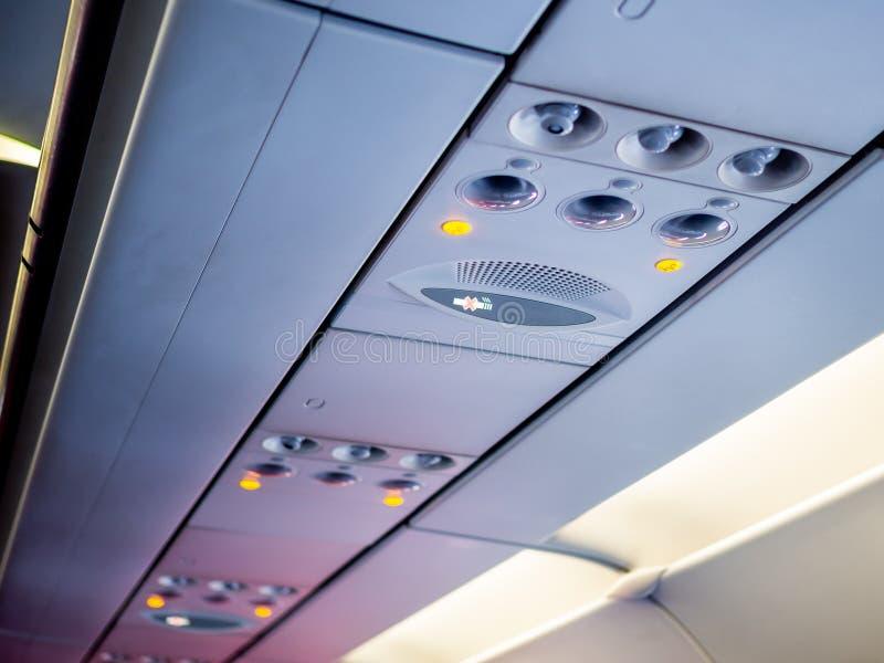 Spese generali ed icone del pannello di controllo nella cabina della classe economica in aeroplano per regoli il condizionamento  fotografia stock libera da diritti