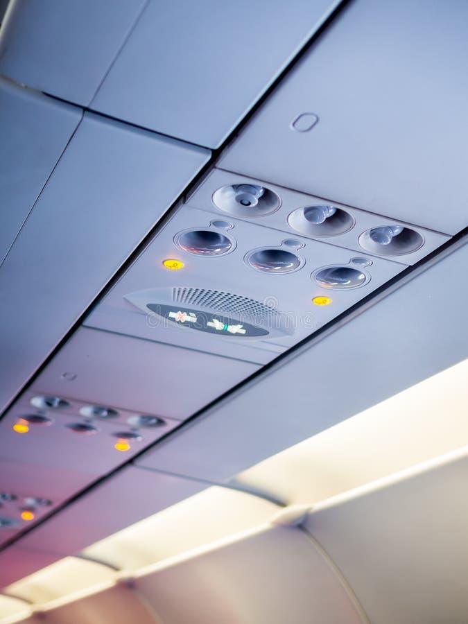 Spese generali ed icone del pannello di controllo nella cabina della classe economica in aeroplano per regoli il condizionamento  fotografie stock libere da diritti