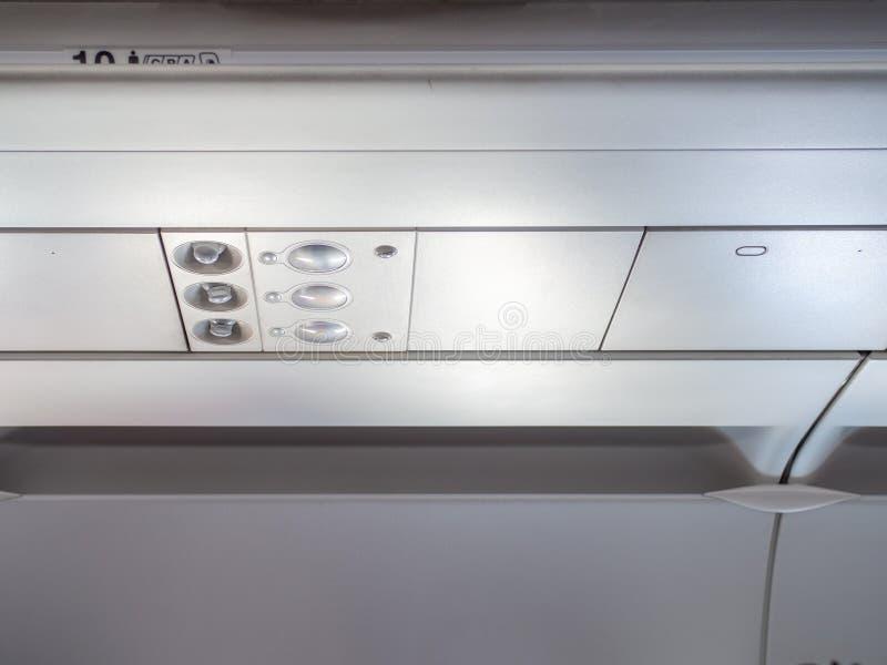 Spese generali ed icone del pannello di controllo nella cabina della classe economica in aeroplano per regoli il condizionamento  immagini stock