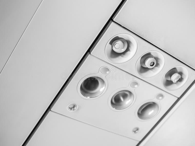 Spese generali ed icone del pannello di controllo nella cabina della classe economica in aeroplano per regoli il condizionamento  fotografie stock