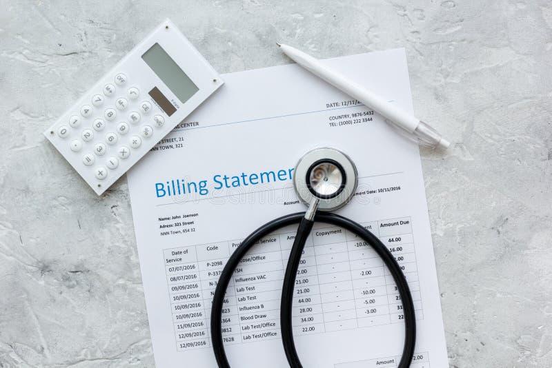 Spese sanitarie con la dichiarazione, lo stetoscopio ed il calcolatore di fatturazione sulla vista di pietra del piano d'appoggio fotografia stock libera da diritti