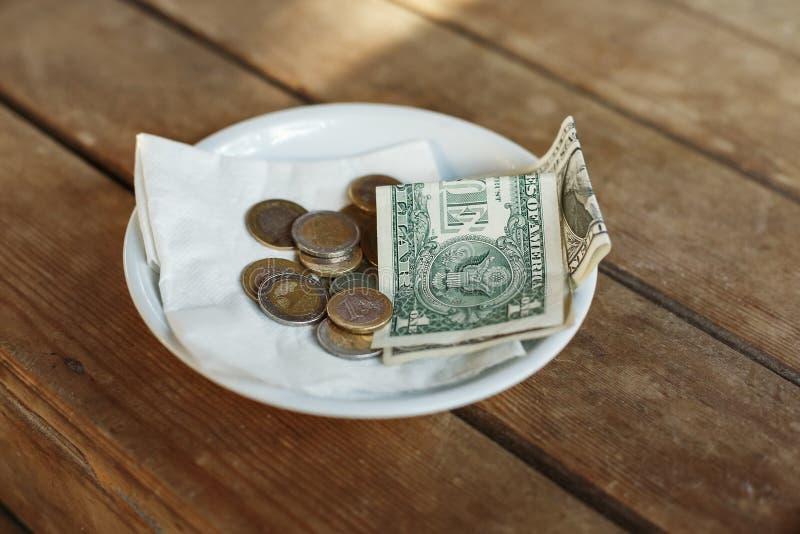 SPETSAR pengar som lämnas på tabellen för server arkivfoto