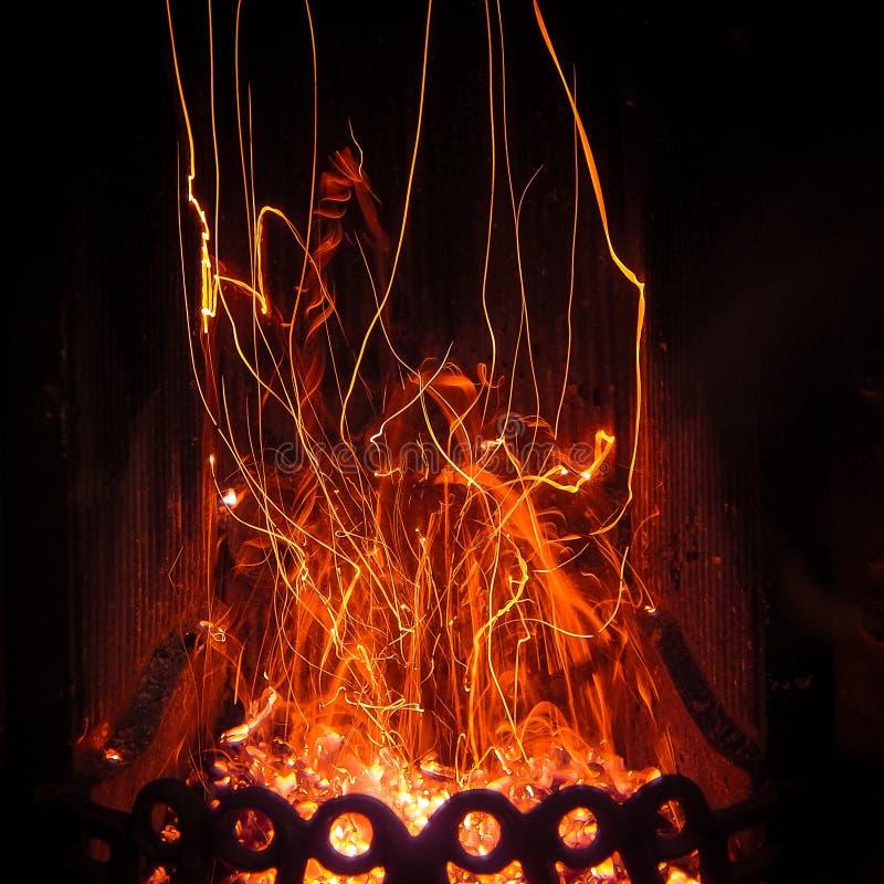 Spettacolo affascinante del ballo magico bizzarro delle scintille e del fuoco nell'inserzione del camino fotografia stock