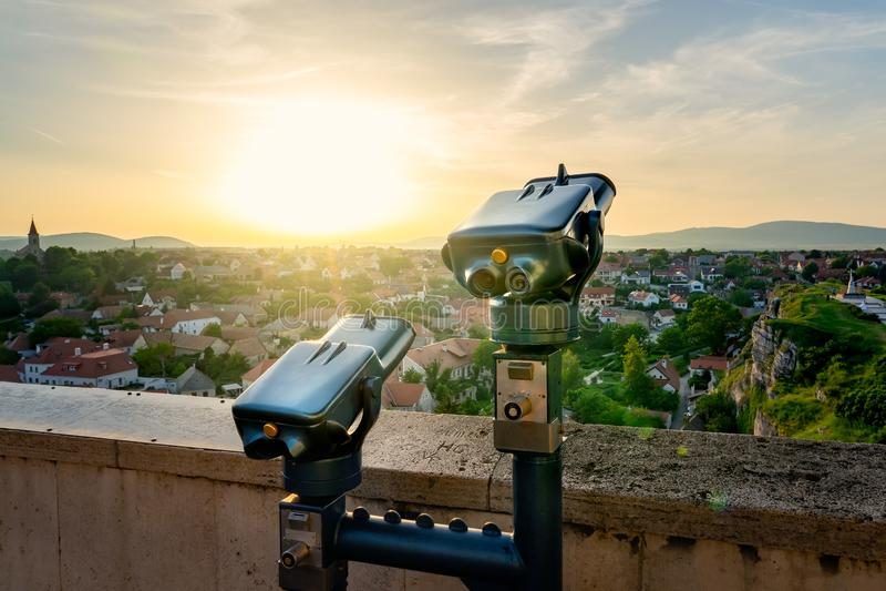 Spettatore binoculare a gettoni accanto al giardino della collina verde in mezzo alla vecchia città Veszprem, Ungheria al tramont immagine stock