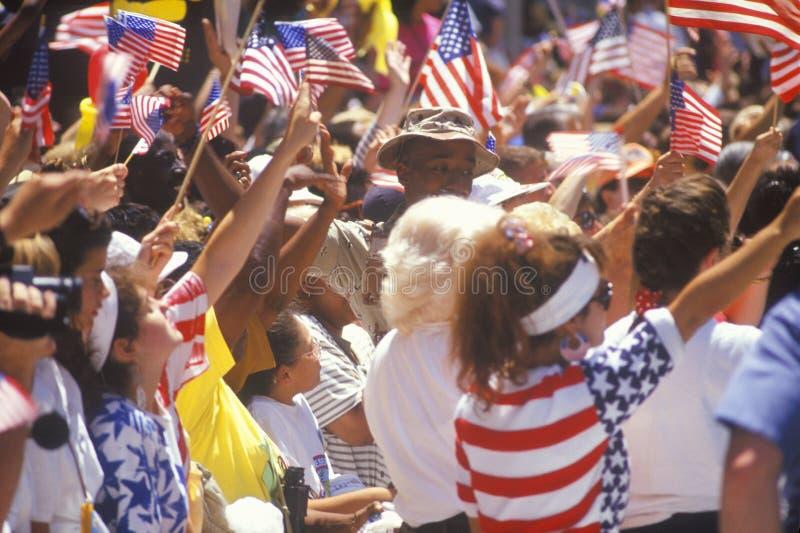 Spettatori che fluttuano le bandiere americane fotografia stock