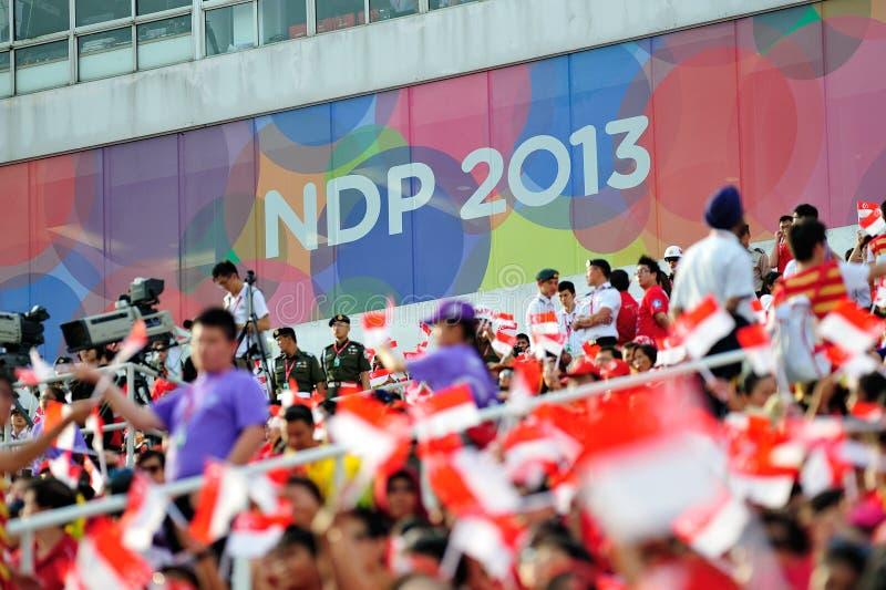 Spettatori che ondeggiano le bandiere di Singapore durante la ripetizione 2013 di parata di festa nazionale (NDP) immagini stock libere da diritti