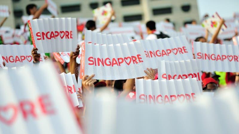 Spettatori che ondeggiano le insegne di Singapore durante la ripetizione 2013 di parata di festa nazionale (NDP) fotografie stock libere da diritti