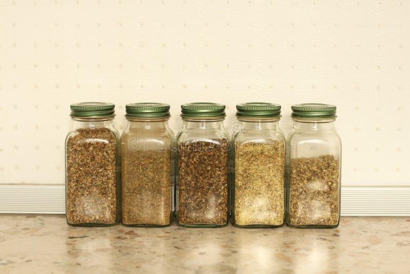 Spezie in barattoli di vetro su un fondo leggero nella cucina Basilico, origano, erbe italiane copi lo spazio per il vostro testo fotografie stock