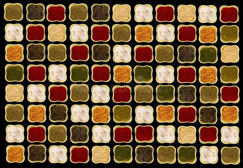 Spezie in ciotole ceramiche verdi quadrate sull'immagine di contrapposizione del fondo nero fotografia stock