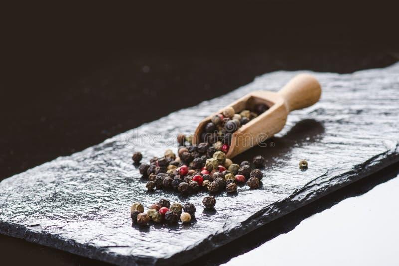 Spezie differenti del pepe su un'ardesia nera Ingredienti per cucinare Concetto sano di cibo Varie spezie su fondo scuro guar fotografia stock libera da diritti