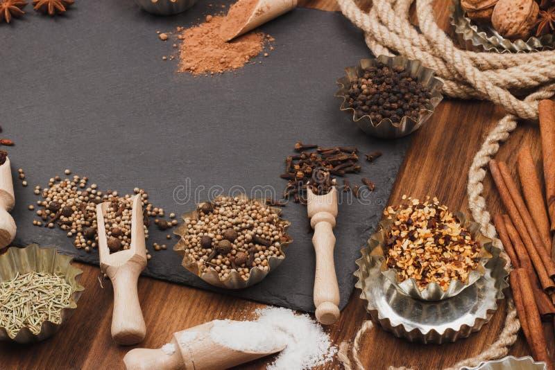 Spezie differenti nel bakeware con i mestoli di legno sui precedenti di slone dell'ardesia fotografia stock libera da diritti