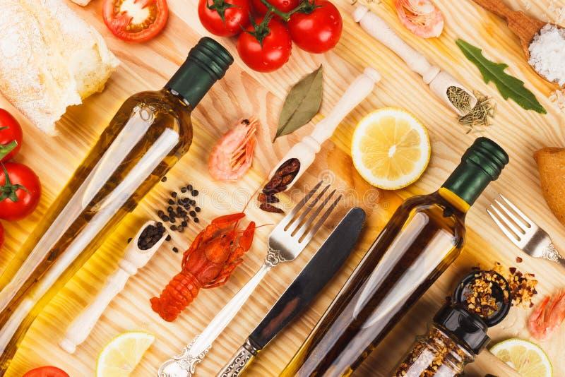 Spezie e argenteria differenti fra le bottiglie di vetro di olio d'oliva immagini stock