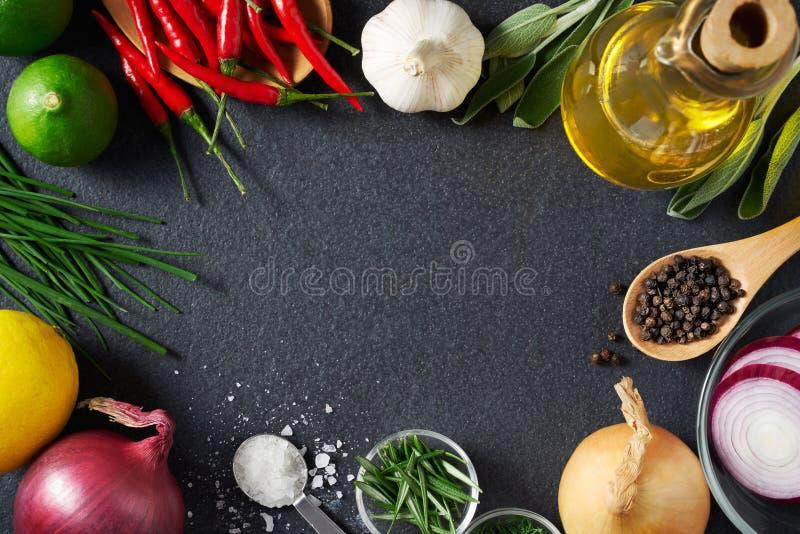 Spezie e ingredienti alimentari sul fondo dell'ardesia fotografie stock