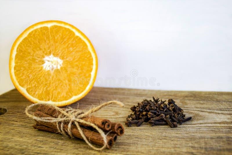 Spezie ed arancia fresca affettata su un tagliere di legno anziano Arancia, bastoni di cannella e chiodi di garofano maturi su fo immagine stock libera da diritti