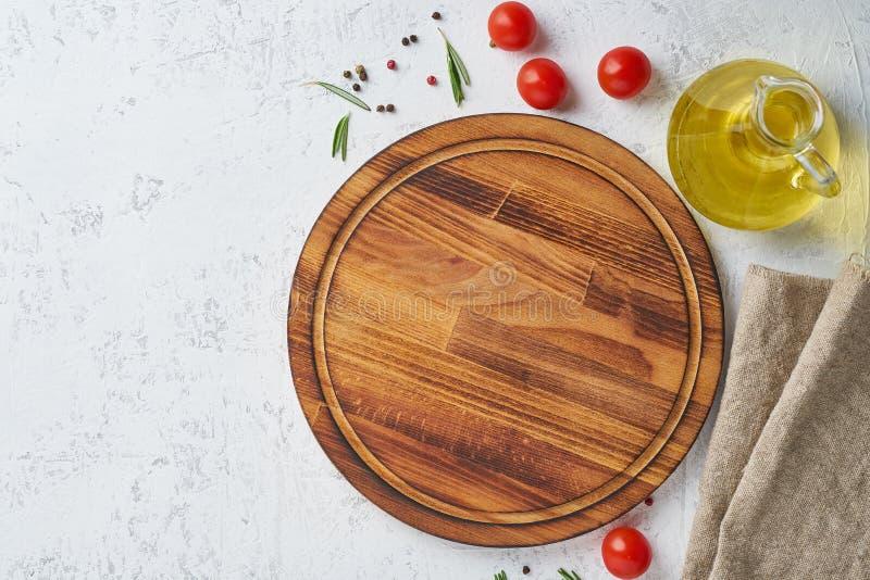 Spezie, erbe e tagliere di legno rotondo sul contesto concreto bianco Vista superiore, spazio della copia Menu, ricetta, falsa su fotografie stock