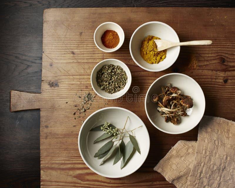 Spezie, funghi e foglie in ciotole bianche su un tagliere di legno rustico fotografia stock libera da diritti