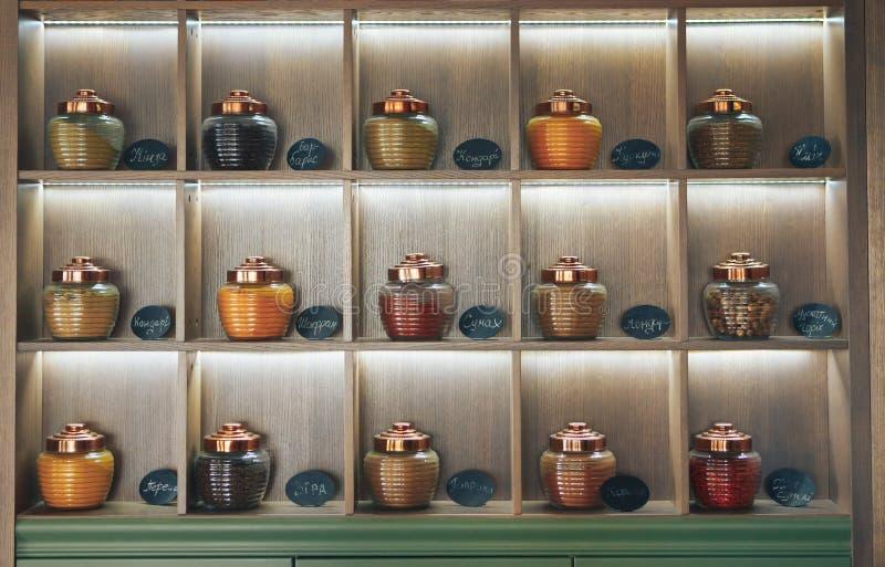 Spezie secche in barattoli di vetro visualizzati sugli scaffali Barattoli della spezia sullo scaffale fotografia stock libera da diritti