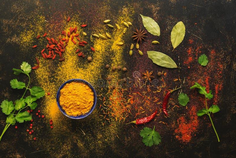 Spezie su un fondo scuro, curcuma, zafferano, cardamomo, peperoncino, paprica, coriandolo, foglia di alloro Varie spezie colorate immagini stock
